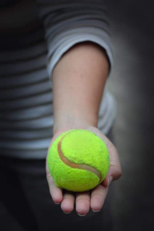 Varrj teniszlabdát a pólójának a hátára