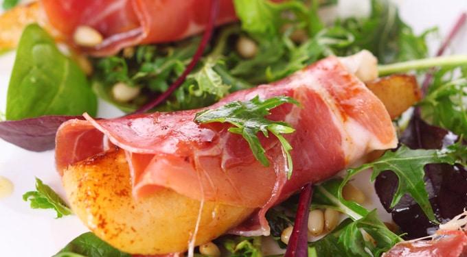 Karamellizált körte és dió prosciutto sonkába tekerve, salátaágyon